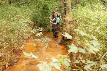 Researchers study Sunday Creek's water quality samples at an acid mine drainage discharge site.