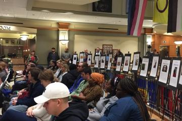 The crowd at the Trans* Day of Remembrance ceremony sits in front of posters of victims of violence in the U.S.
