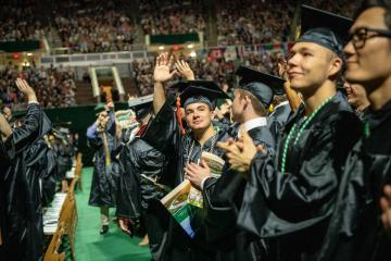 Trent Comfort (Center) waves to supporters during Spring 2019 Undergraduate Commencement. Photo by Ben Siegel