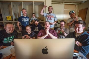 Student team celebrating around a Macintosh computer