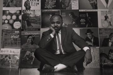 Chuck Stewart sitting in front of a wall of album covers he had taken
