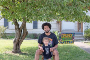 Athens resident Brandon Thompson poses with his daughter in front of their yard sign