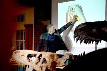 Larry Witmer presents at a science cafe with a dinosaur skull in the forefront