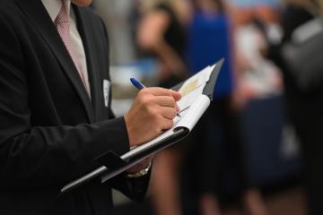 Student taking notes at career fair