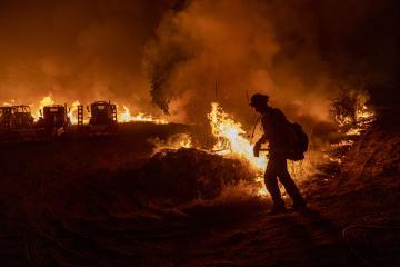 A firefighter battles a blaze in darkness