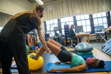 A clinician works with a performing artist using an exercise ball