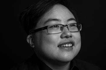 Black and white image of a young East Asian person with glasses smiling and laughing, looking slightly away from the camera