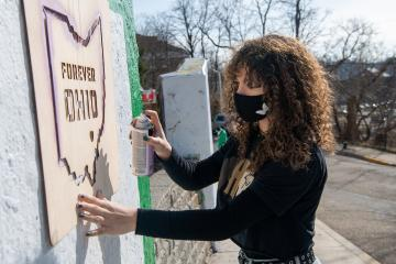 Person placing a stencil with words Forever OHIO and shape of state of Ohio against concrete wall