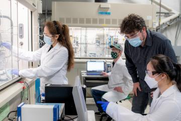 Marc Singer and three students wearing masks work in the lab facility