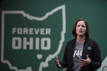 Jenny Hall-Jones speaks at the Leadership Awards ceremony in front of a graphic of the state of Ohio with the words Forever OHIO