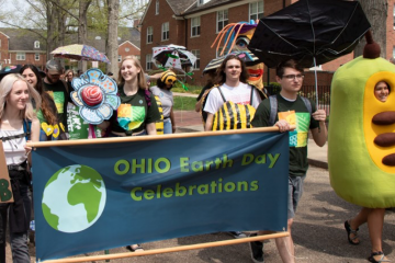 People walk in a parade celebrating Earth Day in 2019