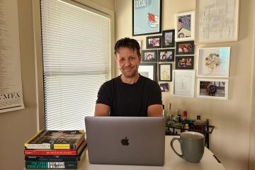 Denis Flaschner sits behind a desk with a stack of books, Apple laptop, mug, with a window and wall of pictures and artwork behind him