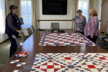 Three women stand around a board table, with two unfinished quilts resting on the table