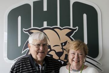 Alumni Tom and Gwen Weihe pose in front of the OHIO logo
