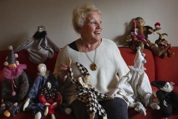 Tilly Berghege smiles around various dolls she has created through the years while sitting on a couch.
