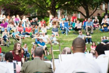 People sitting in grass looking onward and listening to a band