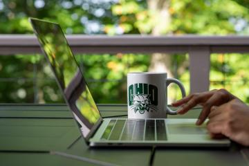 Laptop viewing away to the side, with hands typing away on the keyboard. A white mug with a green Ohio University symbol is seen behind the computer.