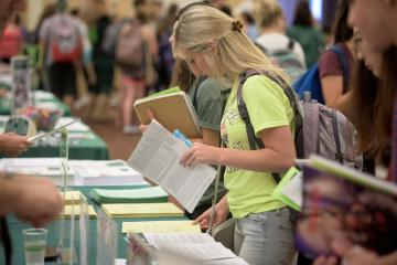 A student looking at flyers at a table while students walk around behind her, looking at other displays