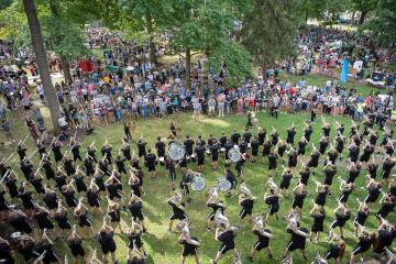 Marching band members play as a crowd of students watch on Ohio University's College Green