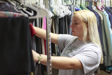 A student with long blonde hair looks through racks of clothing