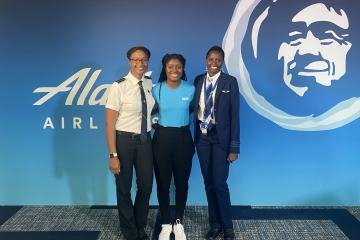 Three women stand together smiling in front of an blue background with Alaska Airlines on it